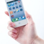 Women's fingers with a manicure keeps White iphone 4 4S on a white
